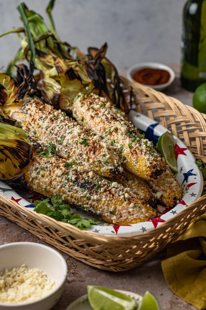 Elotes in a basket. Lime wedges and cotija cheese on the side.