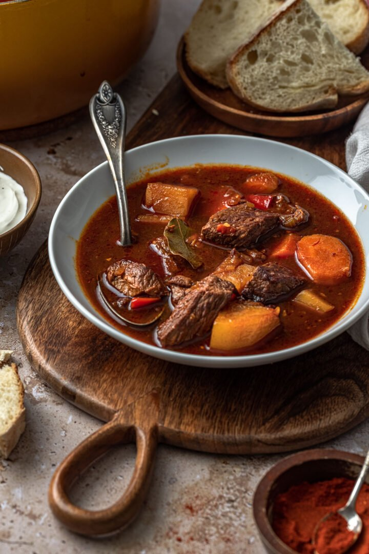 A bowl of Hungarian Goulash, served with a side of bread and sour cream.