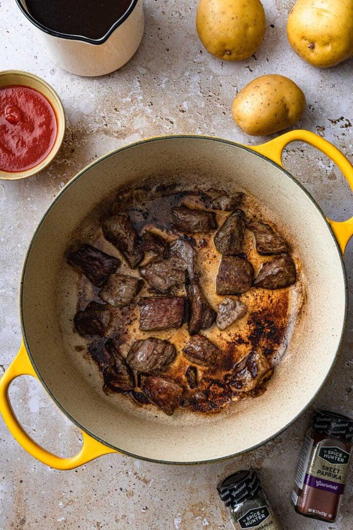 Browned beef in pot.